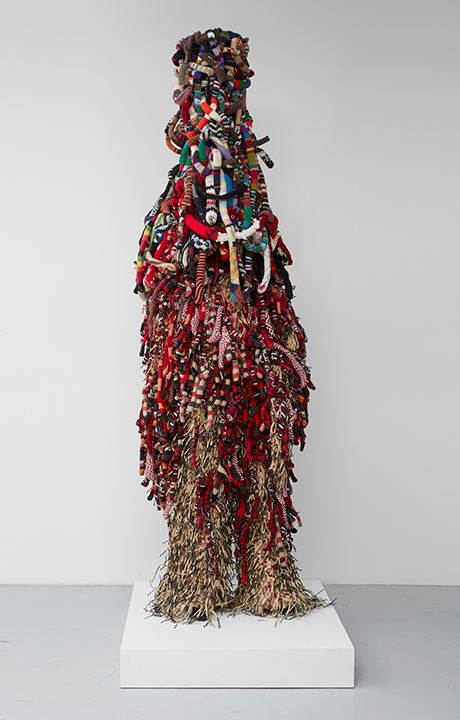 "A tall sculpture made in the form of a ""suit"" using mixed materials including sisal, knitted f"