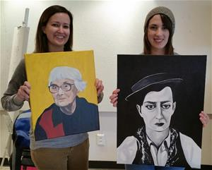 Two female students proudly display portraits created in a painting seminar. One portrait is a color