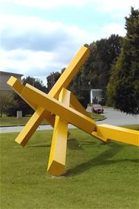 A detail image of a large yellow steel sculpture of various rectangular shapes