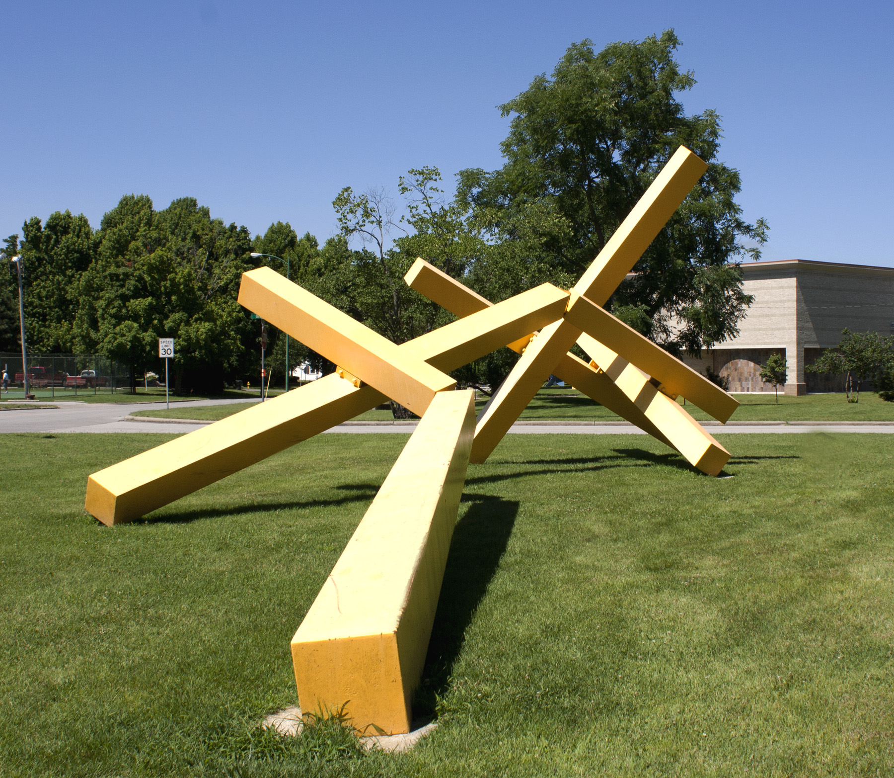 Yellow cor-ten steel sculpture made up of multiple rectangular forms