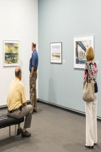 3 patrons viewing waterscapes in the Armstrong Gallery
