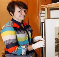 museum assistant Rachel Johnson handles art